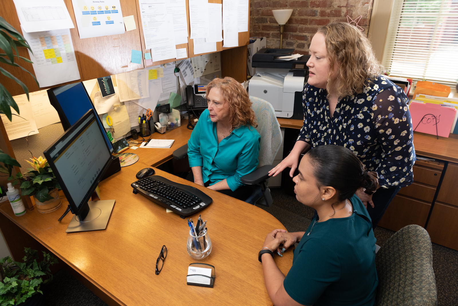 Erin Nagle (standing) discuss PROMOTE software with the School of Psychology's Leslie Dionne-White (left) and Kristie Clark.