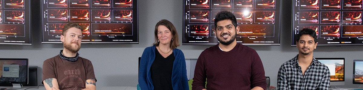 Center for Relativistic Astrophysics Director and School of Physics professor Laura Cadonati (second from left) with members and graduates of the Georgia Tech LIGO research team (from left) James Alexander Clark, Karan Jani, and Sudarshan Ghonge. Behind them, a chart shows gravitational wave signals from cosmic events measured by LIGO-Virgo. (Credit: Allison Carter)