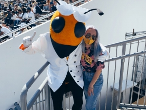 Jess Eskew, Georgia Tech Physics student, poses with Buzz at a football game.